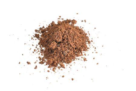 Mound of raw ground cocoa on white