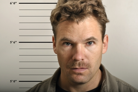 Police mug shot of scruffy man with mustache Stock Photo