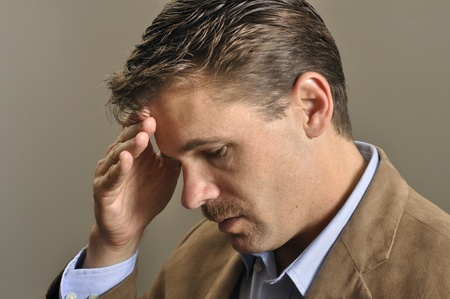 Closeup of depressed man looking down with hand on face Stock Photo - 11767048