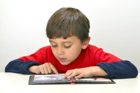 Zes-jarige jongen leesboek aan tafel