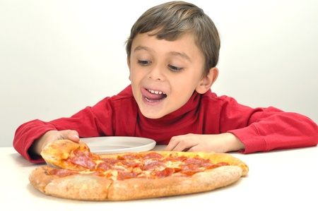 Excited little boy reaches for a slice of pizza photo