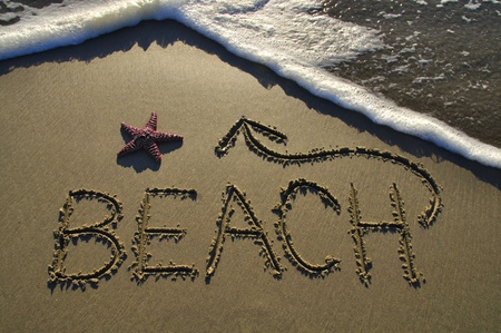 etch: Beach written on sand with arrow and sea star Stock Photo