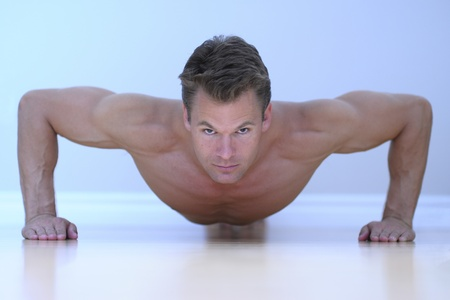 Topless male model performs pushup on floor.