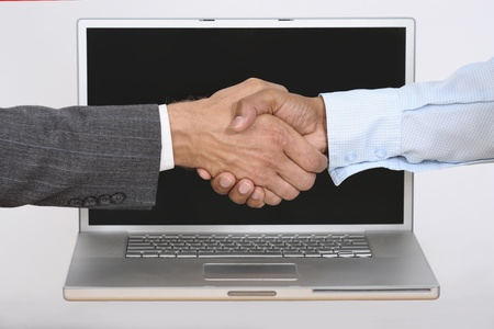 ebay: Caucasion hand shakes Indian hand over laptop computer Stock Photo