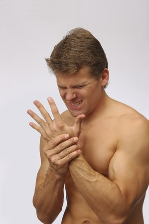 Athletic topless man holds his hand in excruciating pain Stock Photo