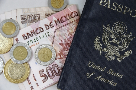consulate: Closeup of Mexican pesos and US passport Stock Photo