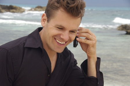Handsome man talks on cellphone at tropical beach photo