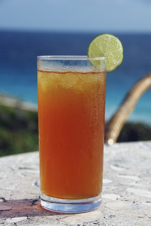 cold: Cold iced tea with lime in tropical setting Stock Photo