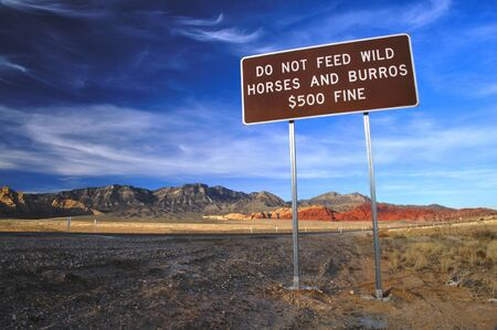 Do not feed wild horses sign in beautiful desert landscape photo