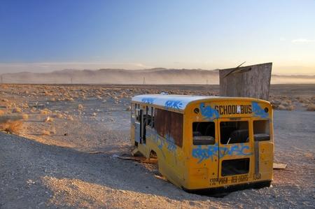 Broken abandoned school bus in sandy desert photo
