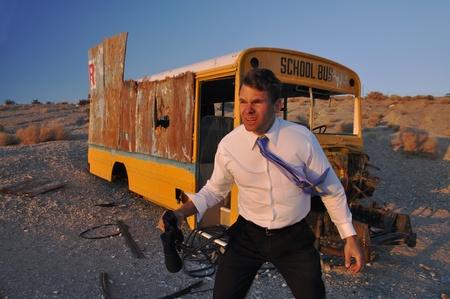 Business man lost in barren desert near abandoned school bus Imagens