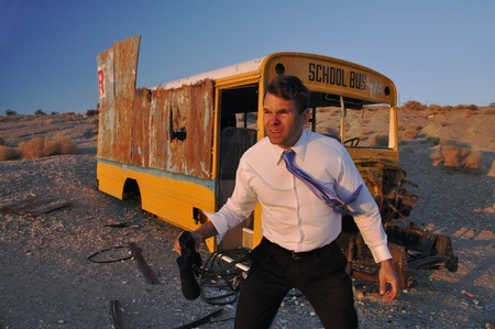 pantalones abajo: Hombre de negocios que perdió en el desierto estéril, cerca de autobús escolar abandonado