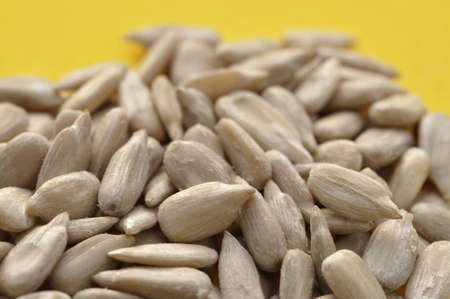 Closeup of raw sunflower seeds on yellow background