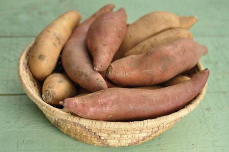 potato basket: Basket of red yams and sweet potatoes on green table