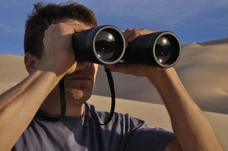 Man looking through big binoculars while exploring desert Stock Photo - 13063376