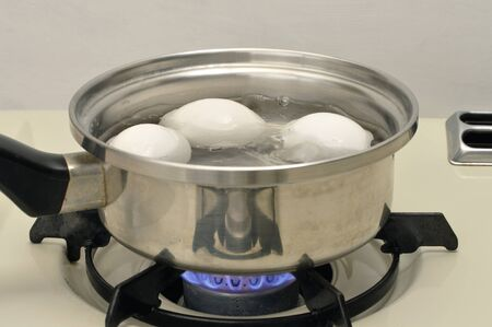 Eggs boiling in pot of water over flame on stove Archivio Fotografico