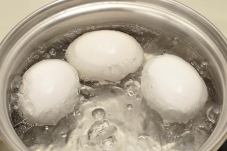 warm water: Close-up van drie eieren koken in pan met heet water Stockfoto