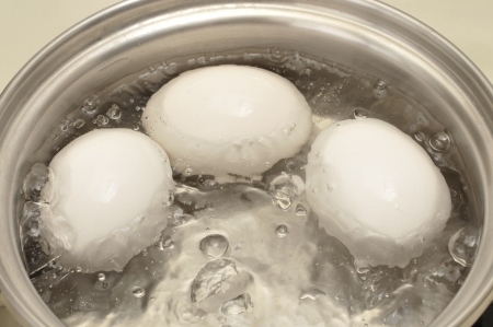 Gros plan de trois bouillir les ?ufs dans une casserole d'eau chaude