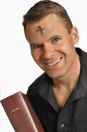 Lachende man met Mark van as op het voorhoofd houdt heilige bijbel