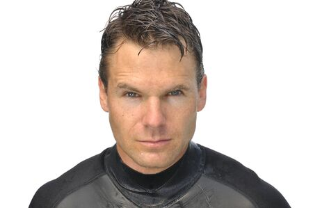 Closeup of handsome dripping wet man in wetsuit with white background photo