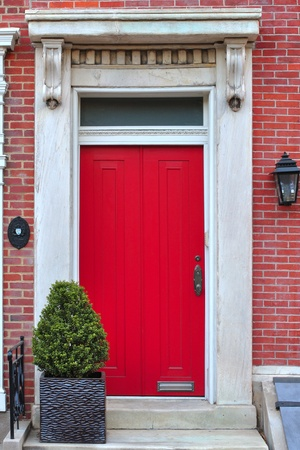Bright red entry door in red brick building photo