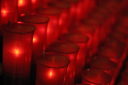 Red sacred offering candles burning in Catholic church photo