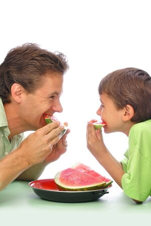 seedless: Father and son eating sliced watermelon together with white background