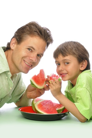 Father and son enjoy eating sliced watermelon together with white background photo