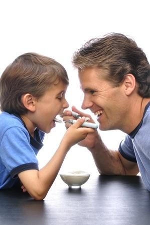 Vader en zoon delen een kom yoghurt samen met de witte achtergrond