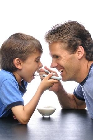 Father and son sharing a bowl of yogurt together with white background Standard-Bild