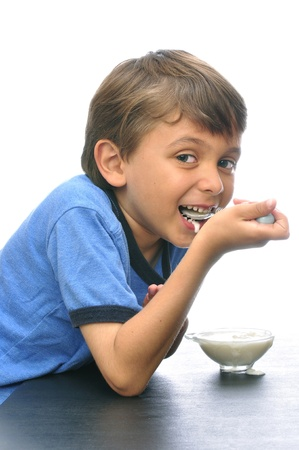 happily: Cute little boy happily eating yogurt with white background Stock Photo