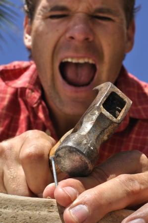 lesionado: Tiro inferior de los dedos del hombre clavado con un martillo Foto de archivo