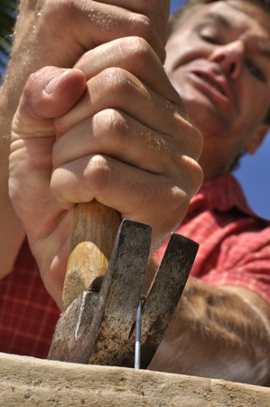 Inferior shot of man struggling to remove nail with hammer photo