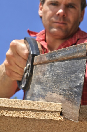 Inferior shot of hard working man sawing wood outdoors Stock Photo - 14056282
