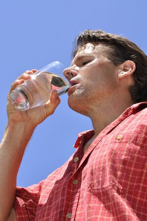 Inferior shot of hot sweaty thirsty man drinking a glass of water photo