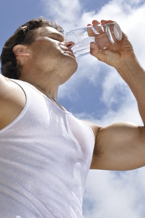 Inferior shot of sweaty muscular man drinking glass of water outdoors photo