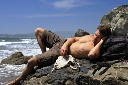 Sexy male vagabond beach bum taking a nap on a rock photo