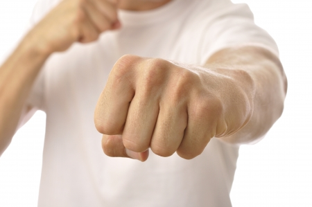 Closeup of fist of unrecognizable man in white T-shirt punching at camera Standard-Bild