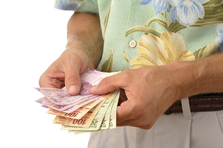 Closeup of unrecognizable male tourist counting handful of pesos, Mexican currency Stock Photo