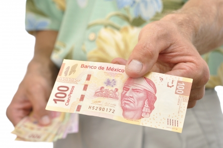 Closeup of 100 pesos in Mexican currency shown by unrecognizable male tourist 写真素材