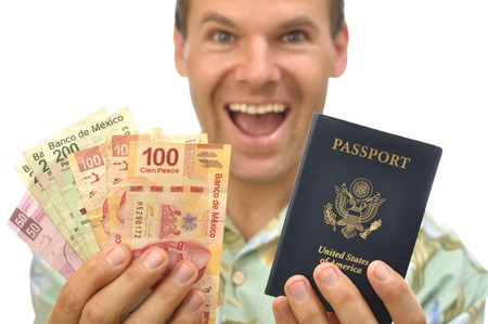 Excited male tourist with handful of pesos and U.S. passport on white background