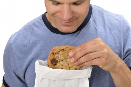 Closeup of man taking a big chocolate chip cookie out of a bag photo