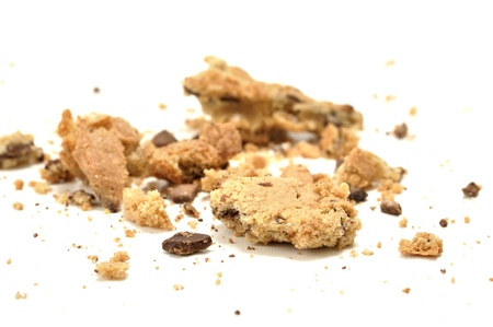biscuits: Closeup of crumbled chocolate chip cookie on white floor Stock Photo