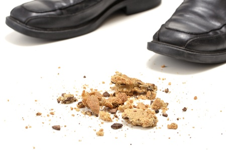 crumbled: Closeup of chocolate chip cookie crumbs on floor with man Stock Photo