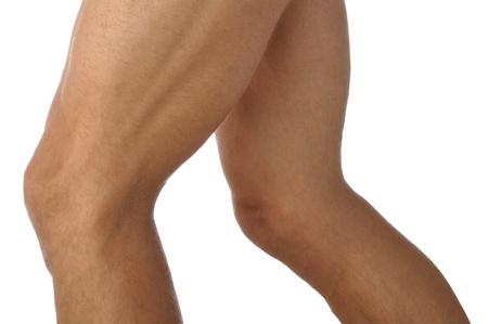 muslos: Primer plano de los atletas masculinos inclinarse musculosas piernas en el fondo blanco Foto de archivo