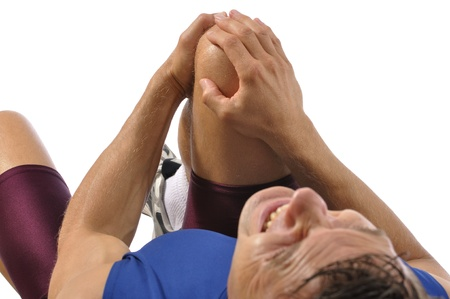 Male athlete lying on floor while clutching knee in excruciating pain on white background photo