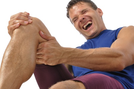 leg injury: Male athlete on floor clutching knee and hamstring in excruciating pain on white background Stock Photo