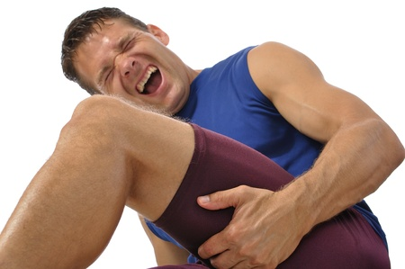 Male athlete clutching his hamstring in excruciating pain on white background Stock Photo