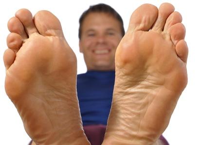 Close-up van de onderkant van de voeten als lachende man reclines op een witte achtergrond