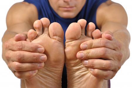 Closeup of bottom of bare feet of male athlete as he holds feet to do hamstring stretch on white background